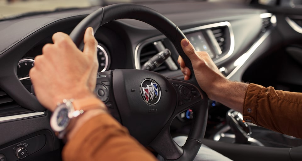 Hands On The Steering Wheel Of The Buick Enclave Mid-Size SUV.