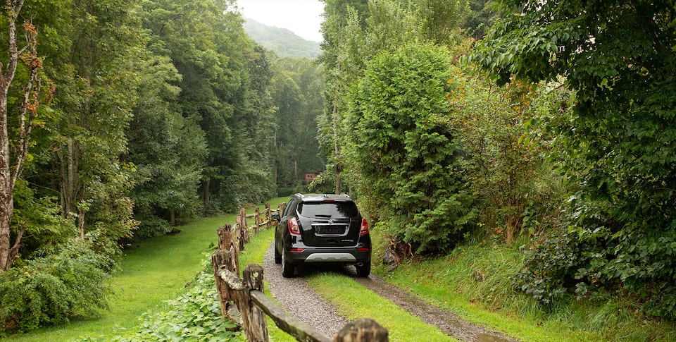 2020 Buick Encore driving between trees.